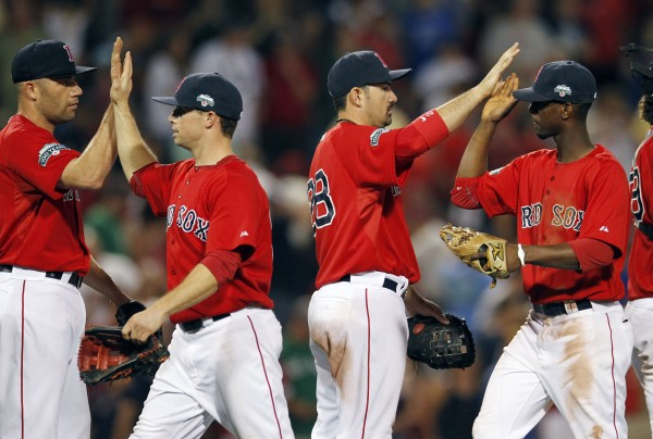 Boston Red Sox players, from left, Alfredo Aceves, Daniel Nava, Adrian Gonzalez and Pedro Ciriaco celebrate after defeating the New York Yankees 9-5 in the second baseball game of a doubleheader in Boston, Saturday, July 7, 2012.