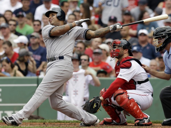 New York Yankees' Andruw Jones follows through on a solo home run as Boston Red Sox catcher Kelly Shoppach watches in the fourth inning of the first baseball game in a day-night doubleheader at Fenway Park in Boston on Saturday, July 7, 2012.