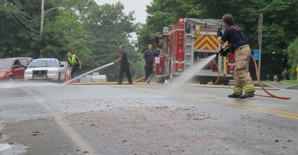 Two Ellsworth firefighters pressure-spray Bucksport Road near the intersection with Route 172 in Ellsworth on Tuesday, July 17, 2012, after an unidentified bait truck spilled some of its load of herring heads, making for slippery, dangerous road conditions.
