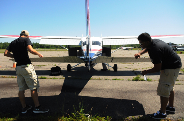 Kyle Hayes (left) of Pensacola Florida and Ameen Thonge (right) of New Jersey perform a  preflight safety check on a Cessna as part of their Civil Air Patrol class in Old Town on Wednesday, July 11, 2012.