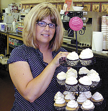 April Braley shows off a few varieties of her Cupcakes Too! desserts.