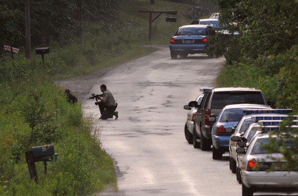 Law enforcement officers crouch down on the pavement of Creamery Road as they get ready to approach a residence on Buck Lane in Hermon on Sunday, July 1, 2012.