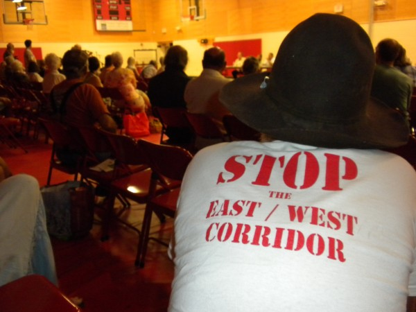 A man against the east-west corridor wears a T-shirt advertising his point of view at a public forum held Saturday, July 14, 2012, at the Ridgeview Community School in Dexter.