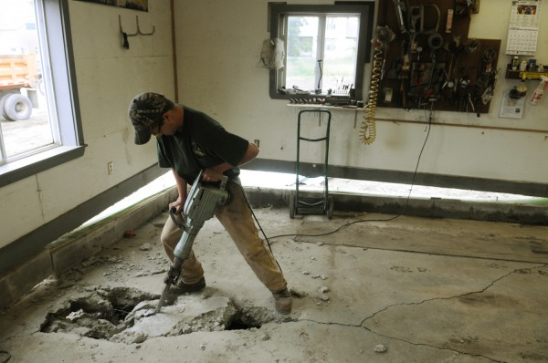 Joseph Arsenault, a worker at Joe's Repair Shop in Brownville, uses a jackhammer on Monday, June 25, 2012, to remove a section of concrete floor that was undermined by flood waters on Sunday.