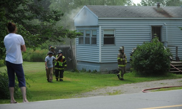 An onlooker stands on the periphery as firefighters from Glenburn, Hudson, Levant and Corinth respond to a fire at this home on Hudson Road in Glenburn on Tuesday afternoon, July 10, 2012. The residence sustained smoke damage.