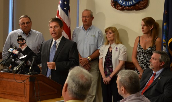 Maine Rep. Kenneth Fredette, R-Newport, (second from left) holds an electronic monitoring device that is capable of alerting domestic violence victims that their abuser may be headed their way. Gov. Paul LePage (from left) looks on as well as Amy Lake's parents, Ralph and Linda Bagley; Dexter teacher Kelley Gay; and Attorney General William Schneider during a press conference in the State House on Friday, July 13, 2012.