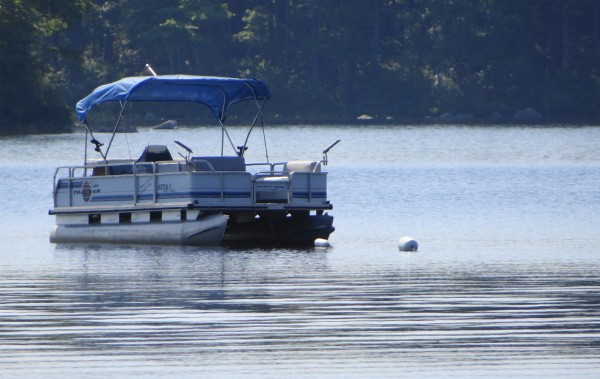 A pontoon boat is anchored on Toddy Pond in Ellsworth off the Toddy Pond campground.