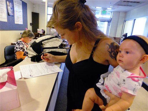 Laura Fritz, 27, left, with her daughter Adalade Goudeseune fills out a form at the Jefferson Action Center, an assistance center in the Denver suburb of Lakewood.