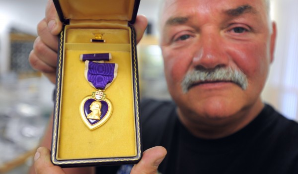 Allen Nadeau holds up a Purple Heart that was awarded to his brother Larry Nadeau after he was killed in Vietnam on January 2, 1966. Allen Nadeau loaned the medal to a traveling exhibit in the late 1990's but it was lost. About 10 years ago it turned up in the coin shop and the owner, Paul Zebiak, returned it to Nedau after learning about the origins of the medal.