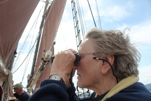 Sailing passenger Flo Hearn of Welsley, Mass., looked through her binoculars to monitor the Great Schooner Race on Friday. Hearn was aboard Angelique, a ketch based out of Camden. She has sailed with that boat for nine summers now.