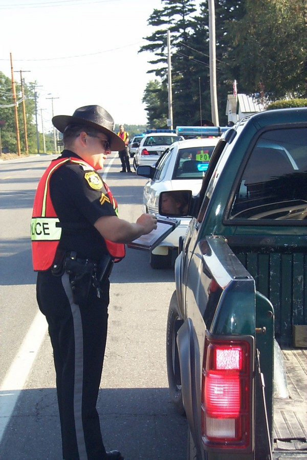 Fairfield police Officer Steven Trahan hands a driver a speeding citation during a special speed-enforcement detail on U.S. Route 201 in the village of Hinckley on Aug. 29, 2000.