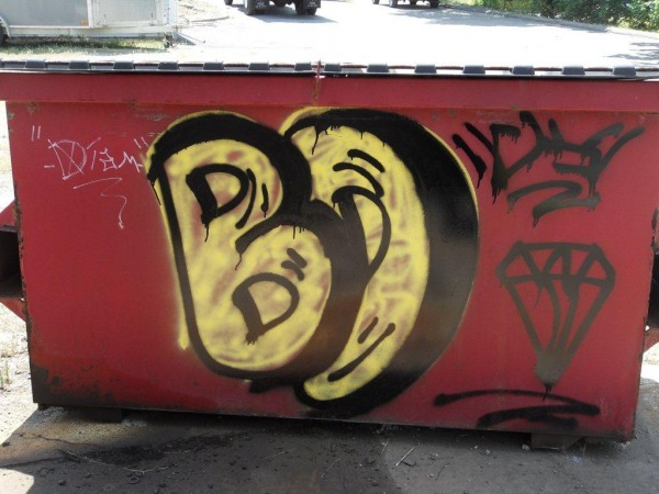A stylized graffiti diamond and the initials &quotB.D.&quot are spray-painted on a Dumpster at Emerson Energy Fuels in Ellsworth on July 16, 2012. Police have issued a summons to a 15-year-old Ellsworth boy in connection with the spate of diamond vandalism around the city in recent weeks.