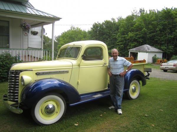 Ralph Ostlund stands outside his New Sweden home with a restored 1939 truck, a gift from his son.