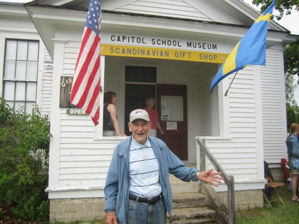 During New Sweden's recent Midsommer Festival, Ralph Ostlund greets people outside the Capitol School Museum, which used to be the Capitol School where he attended school from kindergarten through eighth grade.