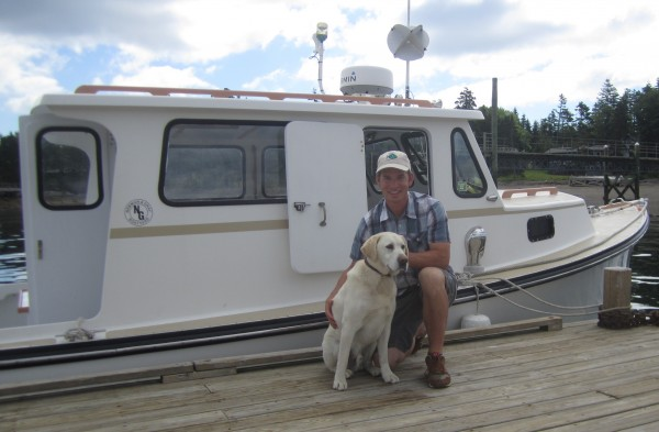 Josh Gray with his deckhand, Ozzie, sit in front the boat that Gray built for his water taxi business, a branch of the Newman and Gray boat building company.