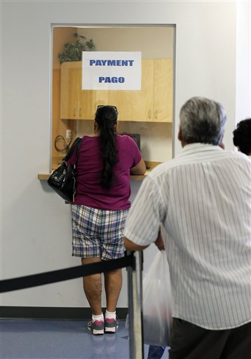 Patients stand in line to make payments at Nuestra Clinica Del Valle in San Juan, Texas.  About 85 percent of those served at the clinic are uninsured. Texas already has one of the nationís most restrictive Medicaid programs, offering coverage only to the disabled, children and parents who earn less than $2,256 a year for a family of three.