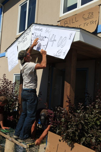 A New Brunswick Lobster fisherman puts up a protest sign on the office of federal Fisheries and Oceans Minister Keith Ashfield in Fredericton on Wednesday, Aug. 8, 2012. Canadian fishermen are protesting the sale of cheap Maine lobster to processors in the province.