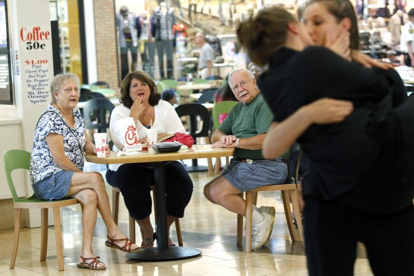 Wanda Flory, of Swanton, Ohio, center, watches with Terry, left, and her husband Richard, center right, who declined to give their last name, as Thea Grabiec, right, kisses Sarah Shovan, Friday evening Aug. 3, 2012,  at the Westfield Franklin Park Mall in Toledo, Ohio. Graviec and Shovan were participating in &quotNational Same Sex Kiss Day at Chick-fil-A,&quot a protest staged in response to &quotChick-fil-A Appreciation Day&quot Aug. 1.