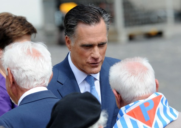 U.S. Republican presidential candidate, former Massachusetts Gov. Mitt Romney speaks with Polish WWII veterans and a survivor of a Nazi concentration camp after laying a wreath at the Warsaw 1944 Uprising monument in Warsaw, Poland, Tuesday, July 31.