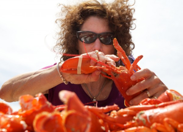 Catherine Davidson of Maryland chows down on as many lobster as she can in 10 minutes during a crustacean eating contest in Portland this summer. Maine is preparing for its second-busiest tourism weekend.