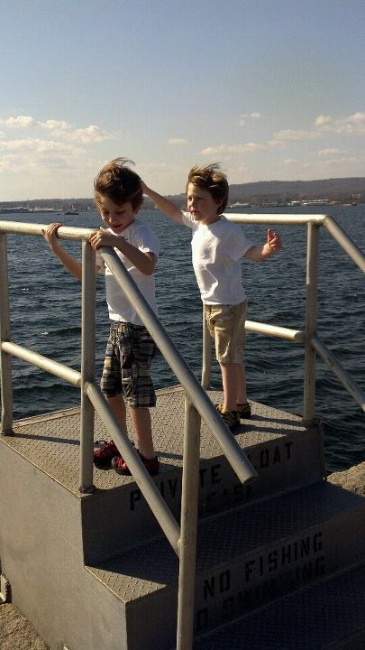Patrick Keene holds onto a staircase on the Rockland breakwater earlier this year next to his fraternal twin brother Noah Keene, who lost his hand in an accident in June.