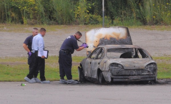 Police examine a vehicle that was found burning with three bodies inside at about 3:35 a.m. Monday parked off Target Industrial Circle in Bangor.