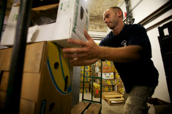 Volunteer Mikel Cameron stacks boxes at the new Wayside Food Programs' facility on Walton Street in Portland on Aug. 15, 2012. The boxes will be filled with food and delivered to needy families in the area.