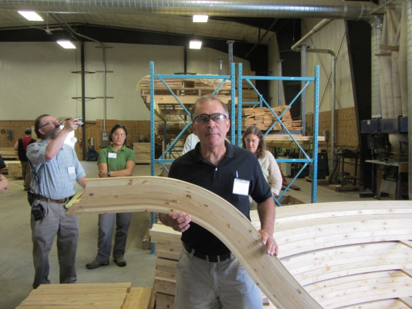 Don Protheroe, plant manager for CedarWorks, shows off a curved piece of cedar that will go into one of the company's play sets.