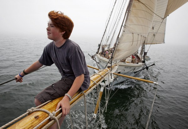 Sawyer King, 12, the son of the captain, rides on the bowsprit of the 90-foot passenger schooner Mary Day while sailing on a foggy afternoon in East Penobscot Bay off Little Deer Isle, Maine.