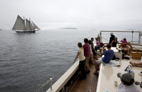 Passengers on the schooner Mary Day, watch the American Eagle sail by on a foggy afternoon on Penobscot Bay off Camden, Maine.