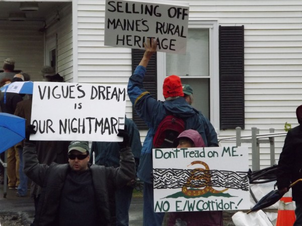 Several people hold up signs protesting the proposed east-west highway while the Piscataquis County Commissioners meeting goes on Tuesday, May 15, 2012, in Dover-Foxcroft.
