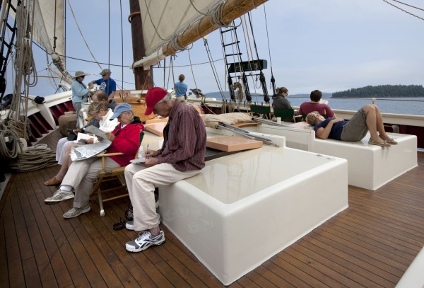 Passengers read, work on crossword puzzles, and just relax on the deck of the schooner Mary Day during a three-day cruise on Penobscot Bay off Camden, Maine