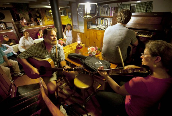 Captain Barry King, on the guitar, joins passengers Sarah Washburn, playing violin, and her husband, Ryan Jesperson, during a musical evening aboard the Mary Day off Ilseboro, Maine.