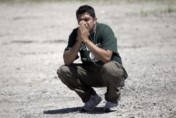 A family member prays in a parking lot while waiting to hear information about his loved ones inside the Sikh Temple on S. Howell Avenue where a shooting occurred on Sunday, Aug. 5, 2012, in Oak Creek, Wis.
