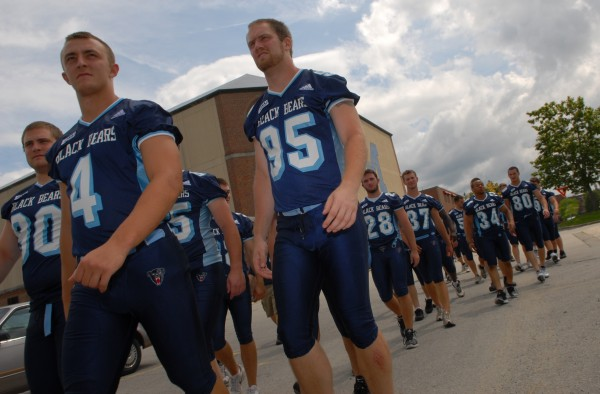 University of Maine football players Derek Buttles (80), Mark Masterson (4) and Al Serena (95) lead the pack out to Morse Field for the team's media day at the University of Maine in Orono Wednesday, August 12, 2009.
