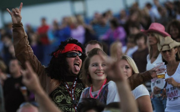 A Poison/Def Leppard fan raises a glass of beer as he and friends take in the '80s hair band along the Bangor Waterfront on Wednesday.