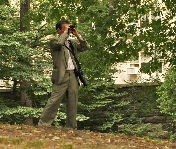 In this June 30, 2012 photo provided by Jean Shum, Jeffrey Johnson uses binoculars to search New York's Central Park for the young offspring of a popular red-tailed Hawk that local birdwatchers know as Pale Male. On Friday, Aug. 24, 2012, Johnson killed a former employer outside the Empire State Building in New York and was himself killed shortly afterwards by police. Nine bystanders were wounded in that chaotic confrontation.