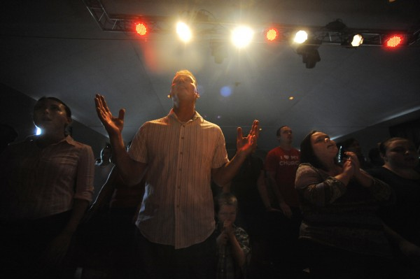 Pastor Kirk Winters (center) prays with his fellow worshipers Sunday morning, Aug. 12, 2012.