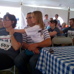 The family of Sarah Robinson, who was honored with the Terry Fox Award posthumously at the Champion the Cure Challenge on Saturday, listens to presenters at the event. Laurel Hartley (left) is comforted by Ben Robinson, Sarah's husband, and Sarah and Ben Robinson's daughter, Morgan Robinson. Robinson's twin sister, Lindsay Turner, and Turner's fiance, Ben Fagan, sit behind them.