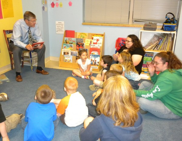 John Bragg, president of N.H. Bragg and Sons, reads a book to students at the Head Start Center at Eastern Maine Community College on June 1, 2011,  just before a press conference where he and other local businessmen stressed the need for early education.