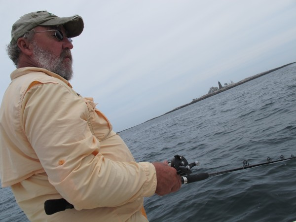 Pete Douvarjo of Eggemoggin Guide Service in Sedgwick fishes from his boat, &quotReel Life,&quot on Tuesday, July 31, 2012. In the background is Mount Desert Rock.