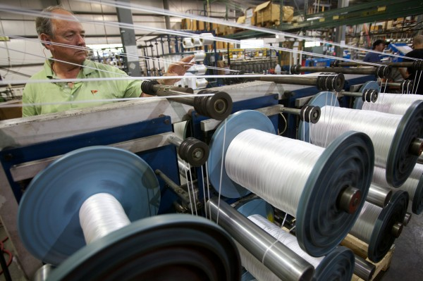 Tom Yale, owner of Yale Cordage, checks up on the machines weaving synthetic line in his Saco factory.