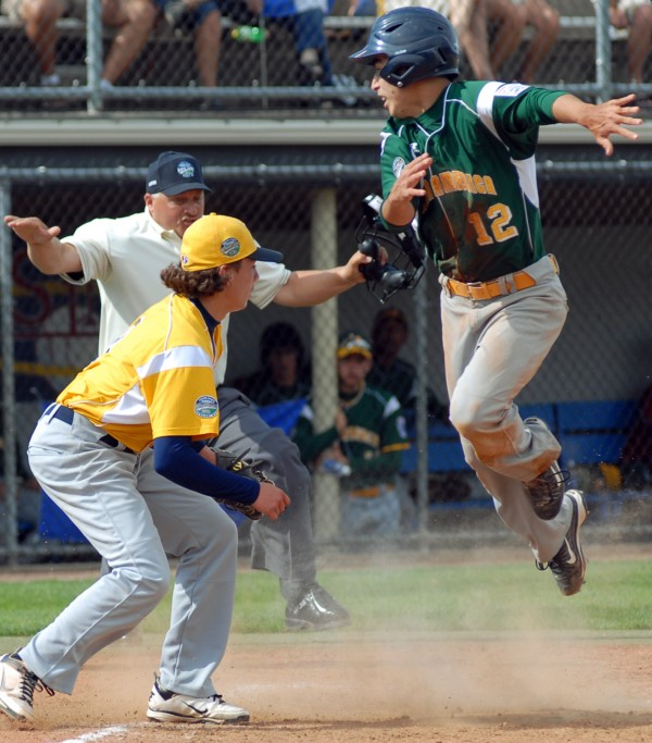 Latin America's Julio Alvarado beats the tag of U.S. West pitcher Brad Moreno at home plate for a run in the 6th inning of the Senior League World Series championship game on Saturday.