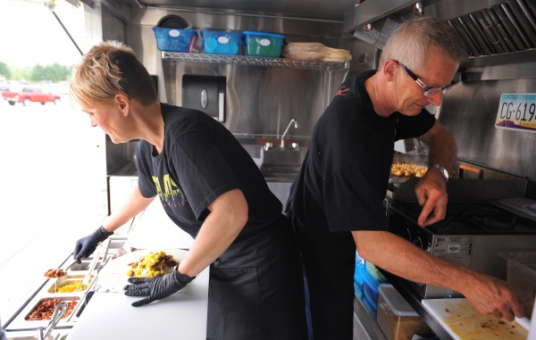 Kirsten Pilot (left) and her husband Chris Pilot prepare food for customers in Cielos Mexican Grill truck Thursday, Aug. 2, 2012. &quotIt was overwhelming, we sold out of everything, but we learned a lot,&quot Kirsten Pilot said about the first day.