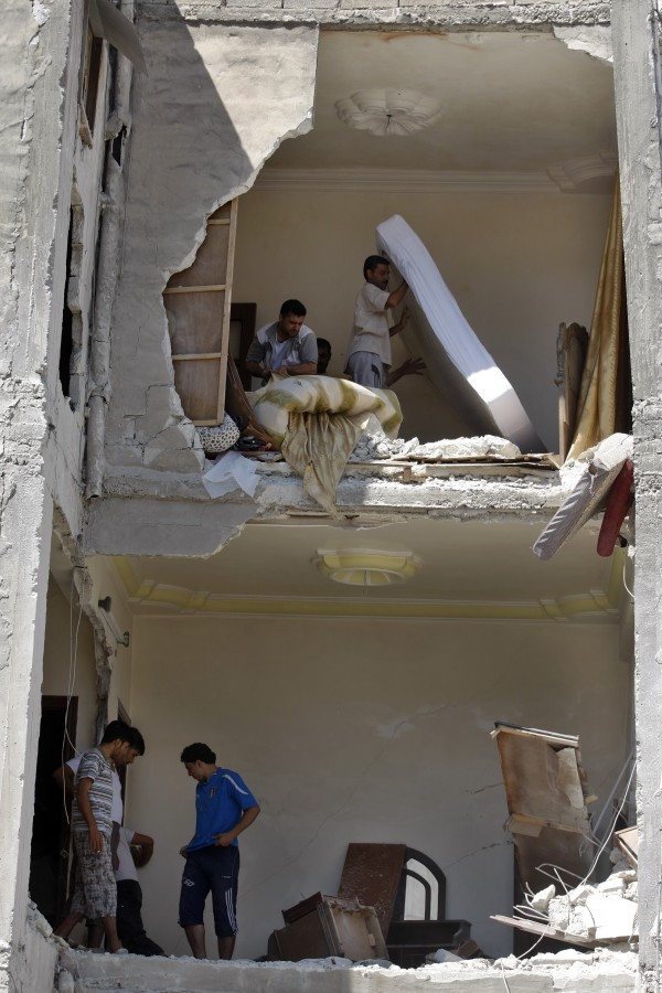 Syrians salvage what they can of their belongings from a building that was hit during a Syrian government air strike in Aleppo, Syria, on Sunday, Aug. 19, 2012.