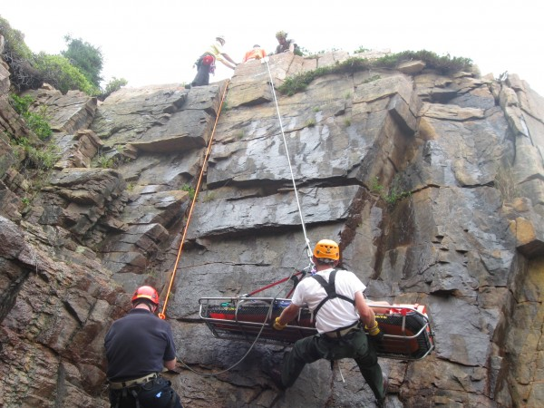 Rescuers move a litter carrying Kevin Hills of Kittery on Saturday, August 18, 2012, in Acadia National Park. Hills fell about 50 feet from a rock face near Sand Beach and reportedly suffered a head laceration, bruises, cuts and scrapes.