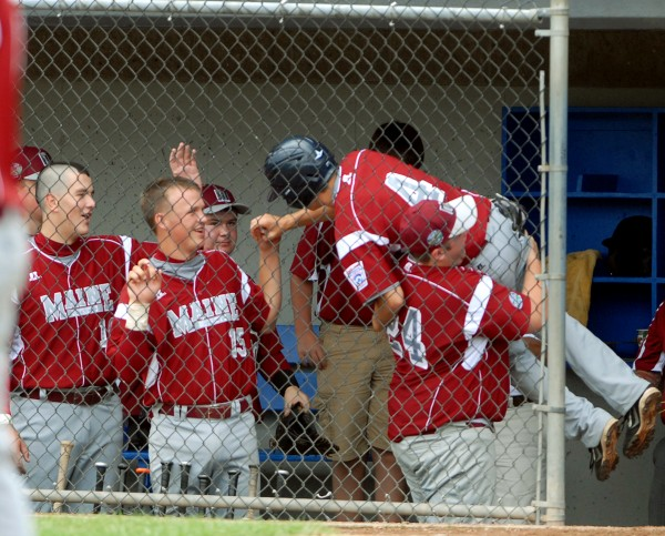 Sam Prescott picks up designated hitter Robert Stowe and celebrates with the team after Stowe scored in the 3rd inning of the Senior Little League World Series opening game against Canada on Sunday afternoon at Mansfield Stadium. Hampden won 9-1.