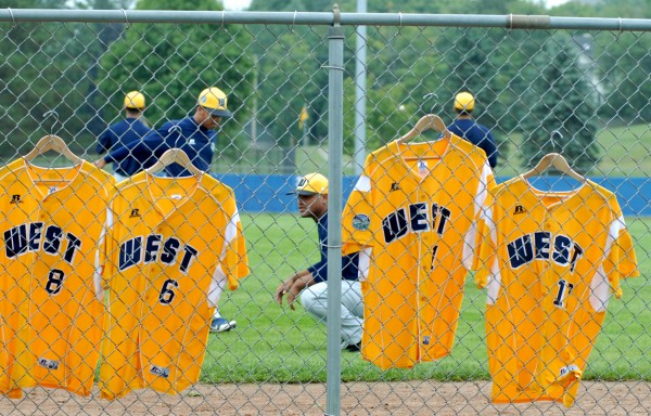 U.S. West jerseys hang on the fence as the team from Lemon Grove, California warms up for their Senior Little League World Series against the U.S Southeast team from Brevard County, Florida on Sunday afternoon.