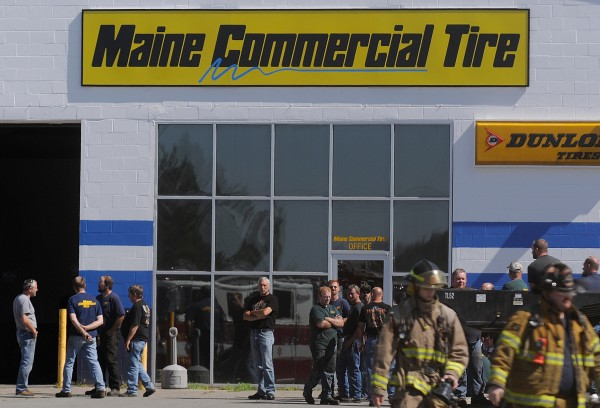 Employees wait to re-enter their work bays as fire crews responded to reports of a fire at Maine Commercial Tire at 55 Freedom Parkway in Hermon Friday morning, Aug. 24. 2012.