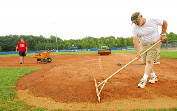 Field crew workers John Stubbs (foreground) and Kyle Savage prep the infield near first base at Mansfield Stadium on Friday morning. The Senior League World Series opening ceremonies take place there Saturday between 7 p.m. and 9 p.m.